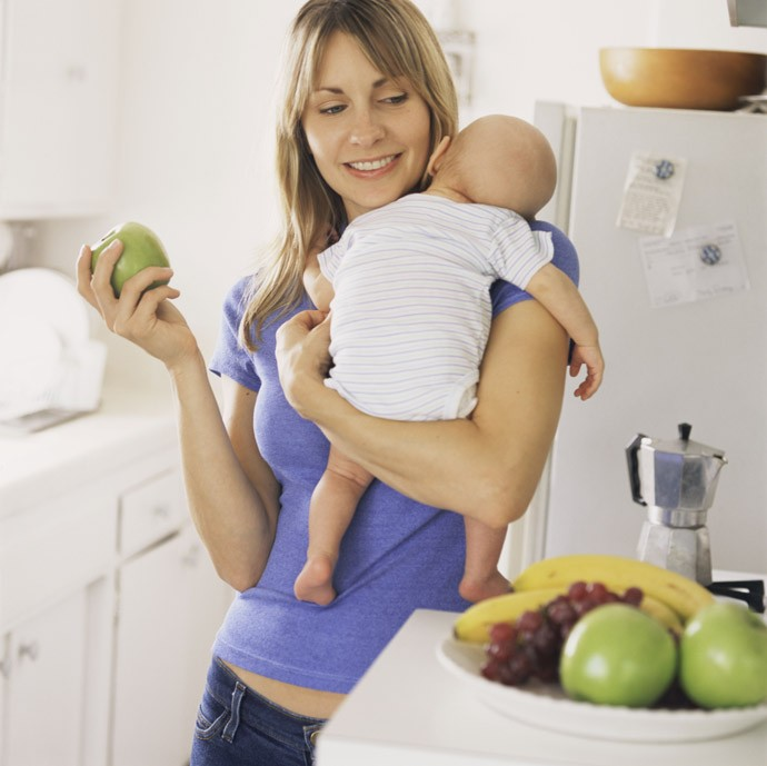Mother Holding Baby in Kitchen with Apple